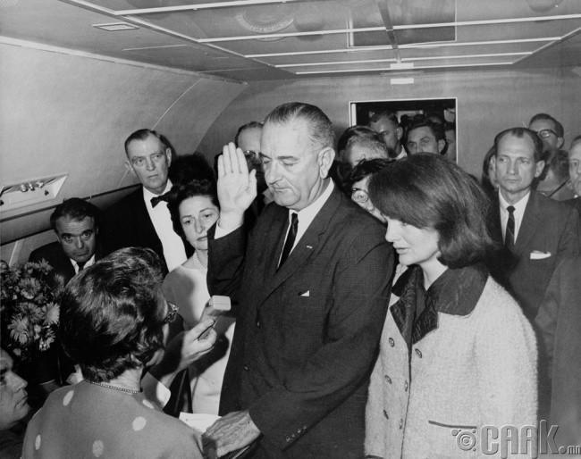 Жон Кеннидиг нас барснаас хэдхэн хоногийн дараа Линдон Жонсон (Lyndon Johnson) ерөнхийлөгчийн тангараг өргөж байна. Түүний хажууд Жон Кеннидигийн эхнэр Жакюлин Жонсон (Jacqueline Johnson) зогсож байна.