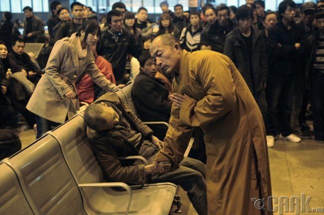 Хятадын Шаньси мужийн галт тэрэгний буудал дээр зуурдаар амьсгал хураасан талийгаачийн хойдохийг уншиж буй лам