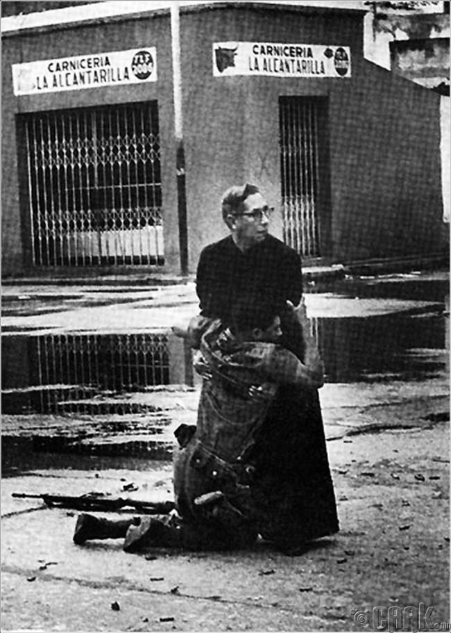 Венесуэл дэх халдлагын үеэр шархадсан цэргийг түшин авч буй номлогч Луис Падилла (Luis Padilla)