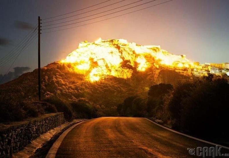 Оройн нарны туяанд шатаж буй мэт харагдах уул