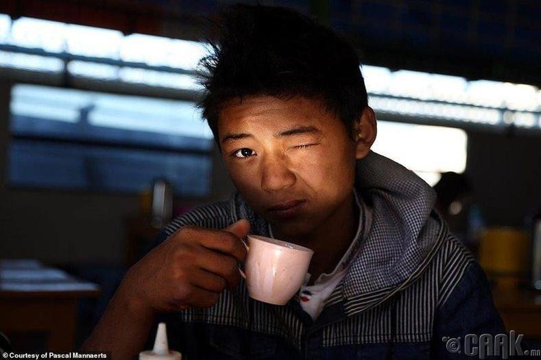 Мьянмарын Кьяйктийо хотод амьдардаг нэгэн залуу өглөөний кофегоо ууж байна