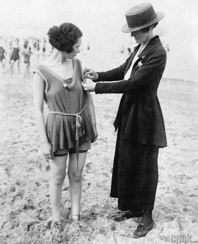 Цагдаа эмэгтэй нэгэн бүсгүйг усны хувцас өмсөхийг хориглосон хууль зөрчсөн эсэхийг шалгаж байна  - Чикаго хот, 1921 он