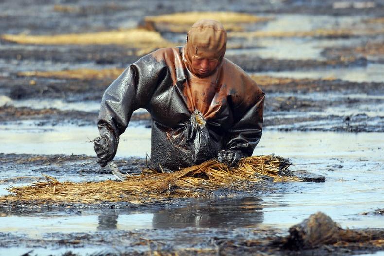 Ляонин хотын Далиан боомтод асгарсан тосыг цэвэрлэж байгаа ажилтан