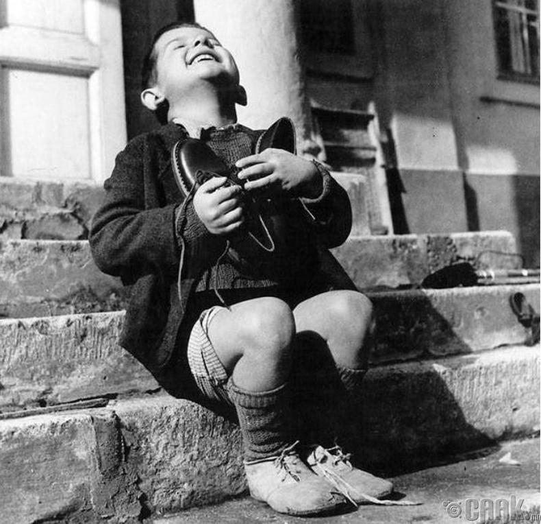 Верфел нэртэй хүү АНУ-ын улаан загалмайн нийгэмлэгээс хандивласан шинэ гутлыг аваад баярлаж байна - 1947 он