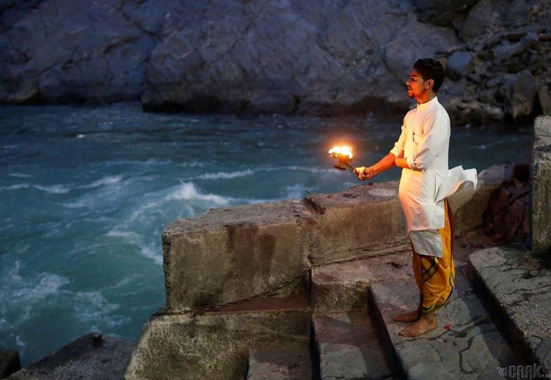 19 настай тахилч Локеш Шарма Гангын эрэг дээр оройн залбирал хийж байна.