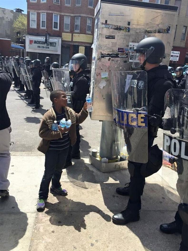 Балтиморын үймээний үеэр халууцсан цагдаа нарт хүйтэн ус өгч буй хүү