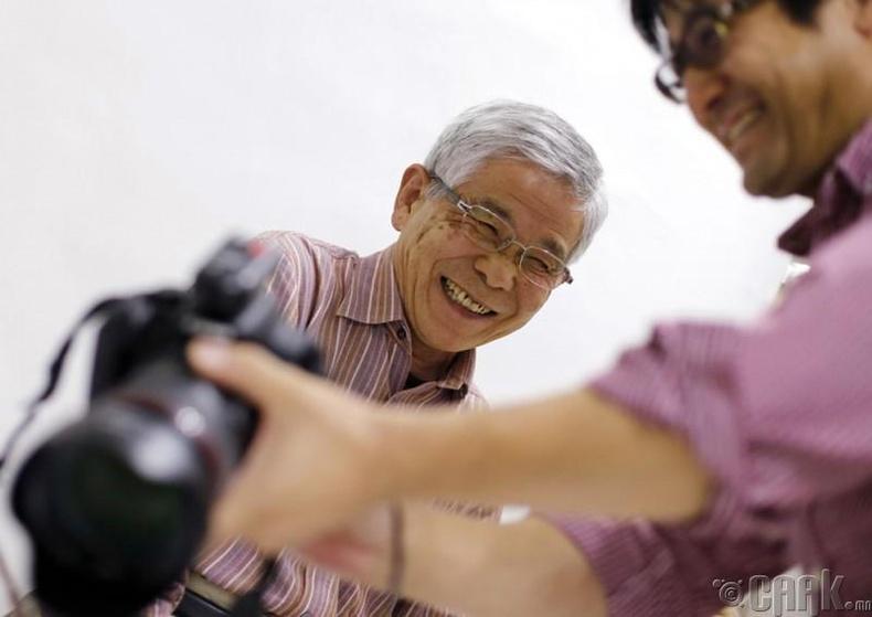 Казуо Фурумото мөн хөрөг зургаа харж буй нь