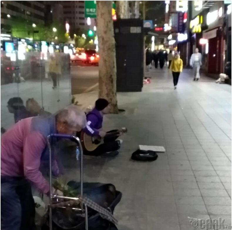 Сөүлд гудамжны тоглолт үзүүлж буй хөгжимчин залуу