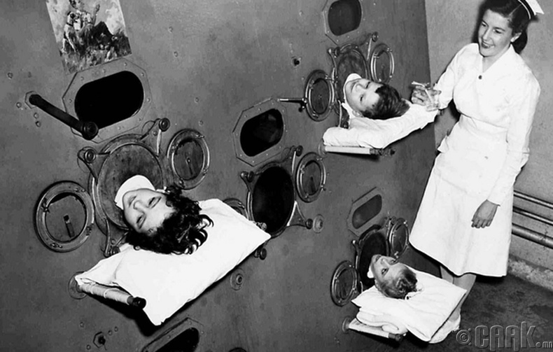 """Полиомелитийн вакцин хийлгэхээс өмнө """"төмөр уушги"""" гэх төхөөрөмжинд орж буй хүүхдүүд, 1950 он"""
