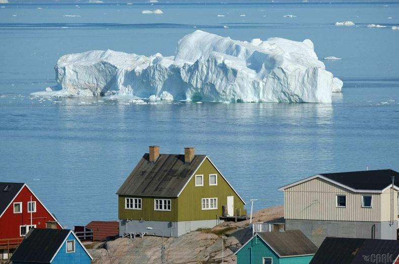 Гренландын Илүлисса дахь байшингуудын араар мөсөн уул хөвж байна