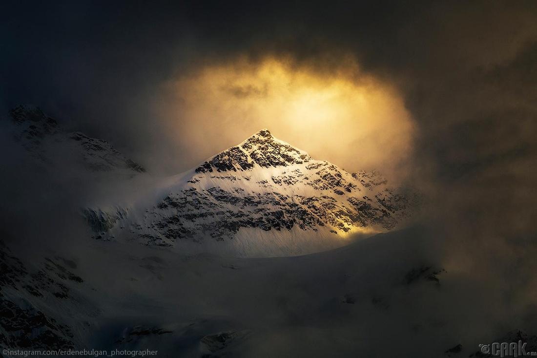 Үүлэн чөлөөгөөр үзэсгэлэнт оргил дээр нарны гэрэл тусах мөч