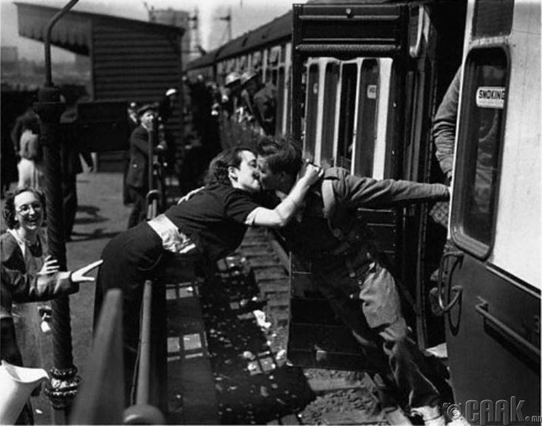 Дэлхийн II дайны үед цэргийн албанд татагдаж байгаа нөхрөө үнсэж буй Англи эмэгтэй