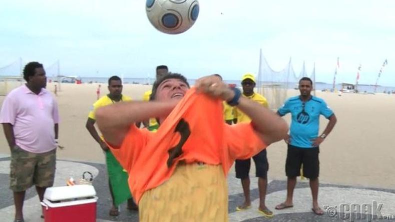 Толгойн дээрээ бөмбөг тогтоож байх зуураа хамгийн олон футболк тайлагч