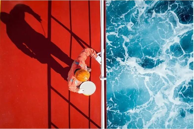 Хөлөг онгоц тээрх хашлага будаж байгаа далайчин