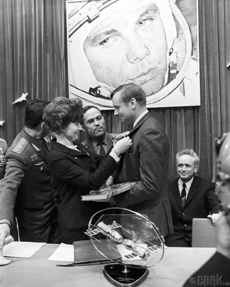 Дэлхийн анхны эмэгтэй сансрын нисгэгч Валентина Терешкова АНУ-ын сансрын нисгэгч Нил Армстронгт хөдөлмөрийн баатрын тэмдэг зүүж өгч байна