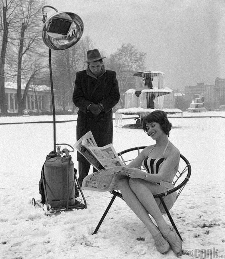 Халаагч лампын хүчин чадлыг үзүүлэх зорилгоор нимгэн хувцастай сууж буй бүсгүй, Герман, 1960 он