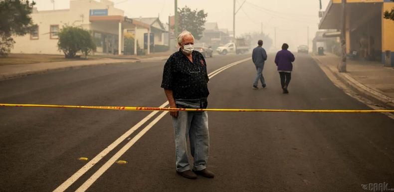 Сүйрсэн байшингаа харж буй оршин суугч, Кобарго хот