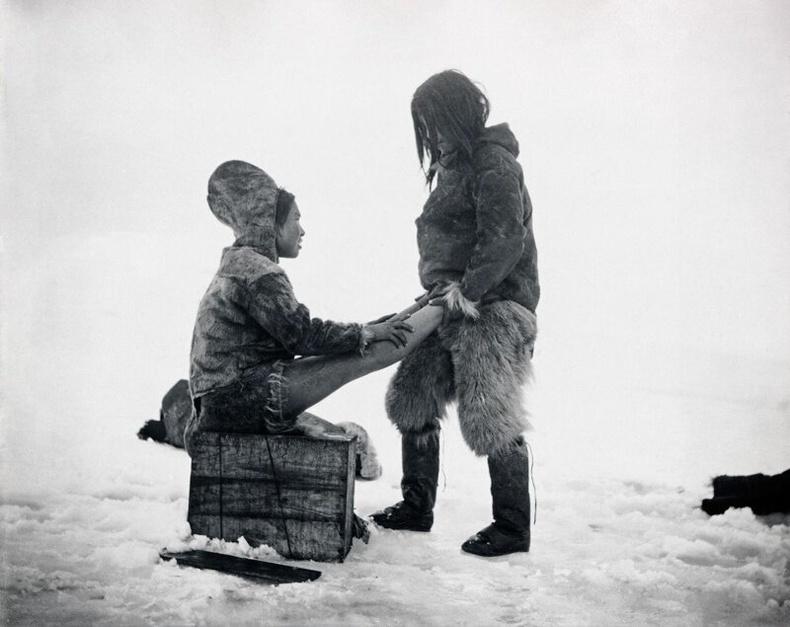 Эхнэрийнхээ хөлийг дулаацуулж буй Инуит эр. Гренланд, 1890