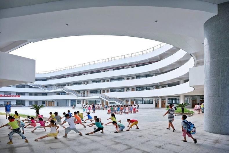 Сургуулийн талбайдаа өглөөний дасгал хийж буй сурагчид
