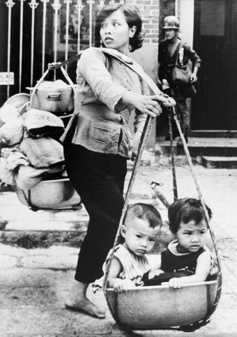 Сайгоны тулалдааны үеэр хулсан сагсанд хүүхдүүдийг авч явж буй Вьетнам эмэгтэй, 1968