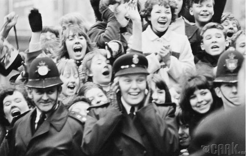 """""""The Beatles"""" хамтлагийн """"A Hard Day's Night"""" киноны зураг авалтын үеэр тэднийг харах гэсэн шүтэн бишрэгчид болон цагдаа нар - 1964 он"""