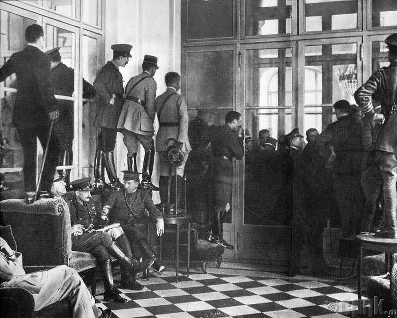 Версалийн энхийн гэрээ-1919 оны 6-р сарын 28-нд Дэлхийн 1-р дайныг албан ёсоор дуусгасан Версалийн гэрээнд гарын үсэг зурахыг харах гэжхүмүүс буйдан, ширээ, сандал дээрээ гарч зогсжээ