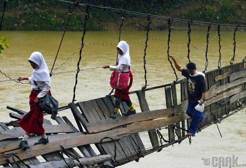 Индонезын Лебакт сурагчид эвдэрхий дүүжин гүүрээр их усыг гатлан хичээлдээ явдаг байв
