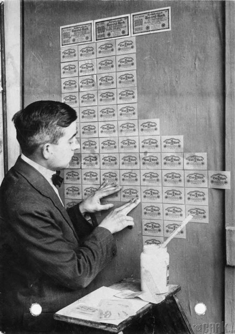 Инфляцын хямралын үеэр мөнгөн тэмдэгтийг ханын цаас болгон ашиглаж буй эр - Герман, 1923 он