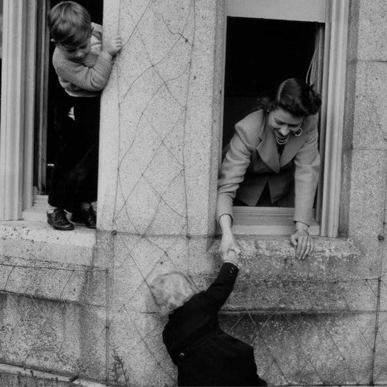 Хатан хаан Элизабет Анна гүнжийг цонх руу авирахад нь тусалж байна. Хажууд байгаа нь Чарльз ханхүү. (1952)