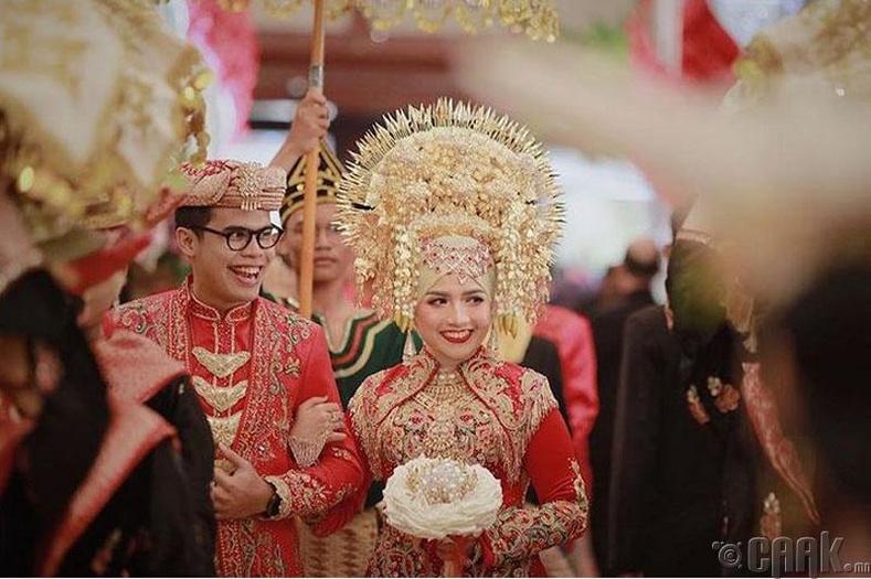 Индонези, тэр дундаа Жакарта хотод хуримлаж буй хосууд гоёмсог хээ угалз бүхий алтадмал хувцас, толгойн гоёл зүүдэг