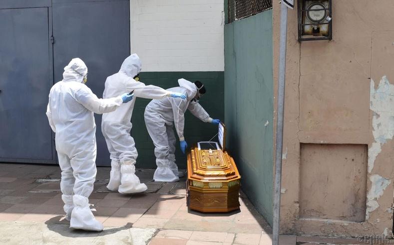 Хамгаалалтын хувцастай ажилтнууд байшингийн гадаа үлдээсэн авсыг авч буй нь, Эквадор, 4 сарын 6