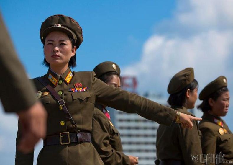 Пхеньян дах Жүчэ Идэагийн (Juche Idea) хөшөөний дэргэд зогсож буй цэрэг эмэгтэй -2012 он