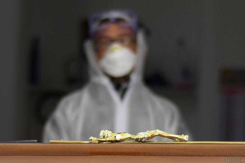 Кистернино хотын оршуулах ёслолын үеэр хоёр коронавирусын хохирогчдын авсыг харж буй ажилтан