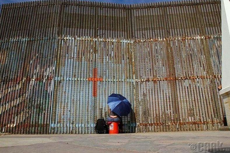 Мексикийн иргэн АНУ-д байдаг хамаатнуудтайгаа хилийн хашааны завсараар уулзаж буй мөч