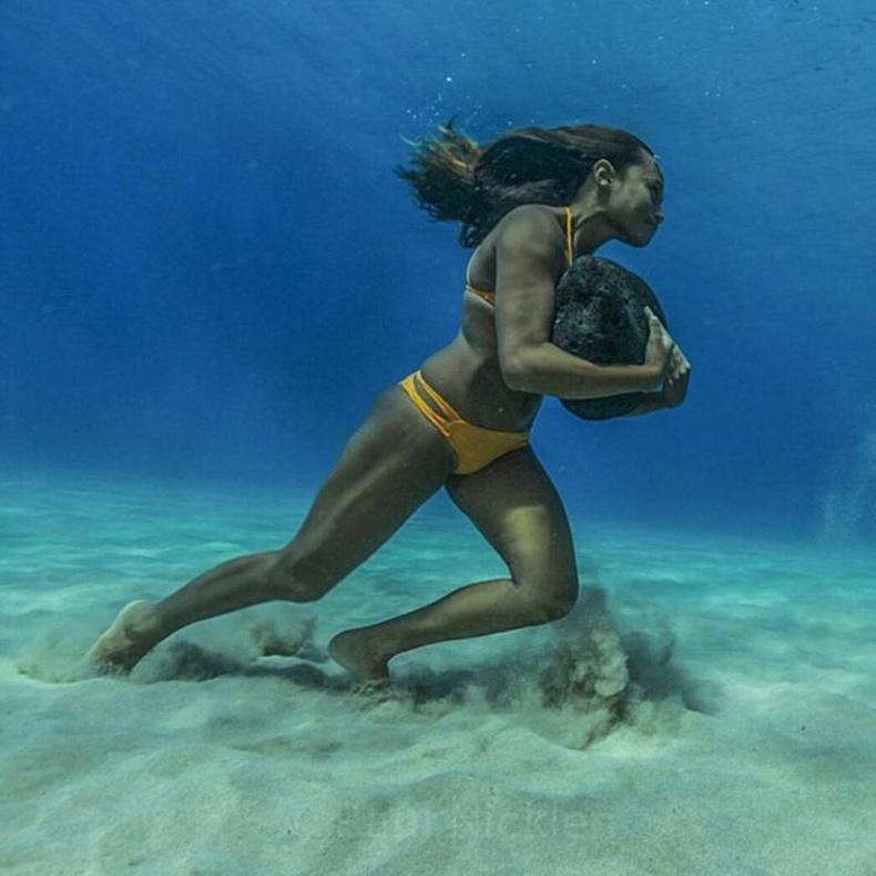 Серфингийн тамирчин бүсгүй усан доор бэлтгэл хийж байна